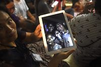 "TOPSHOT - CORRECTION - A family member shows a picture of four of the twelve missing boys near the Tham Luang cave at the Khun Nam Nang Non Forest Park in Mae Sai on July 2, 2018. Twelve boys and their football coach trapped in a flooded Thai cave for nine days were ""found safe"" on late July 2, in a miracle rescue after days of painstaking searching by divers. / AFP PHOTO / LILLIAN SUWANRUMPHA / CORRECTION: ìThe erroneous mention[s] appearing in the metadata of this photo by LILLIAN SUWANRUMPHA                  has been modified in AFP systems in the following manner: [A family member shows a picture of four of the twelve missing boys near the Tham Luang cave at the Khun Nam Nang Non Forest Park in Mae Sai on July 2, 2018.] instead of [A happy family member shows the latest pictures of the missing boys taken by rescue divers inside Tham Luang cave when all members of children's football team and their coach were found alive in the cave at  Khun Nam Nang Non Forest Park in the Mae Sai district of Chiang Rai province late July 2, 2018]. Please immediately remove the erroneous mention[s] from all your online services and delete it (them) from your servers. If you have been authorized by AFP to distribute it (them) to third parties, please ensure that the same actions are carried out by them. Failure to promptly comply with these instructions will entail liability on your part for any continued or post notification usage. Therefore we thank you very much for all your attention and prompt action. We are sorry for the inconvenience this notification may cause and remain at your disposal for any further information you may require.î"