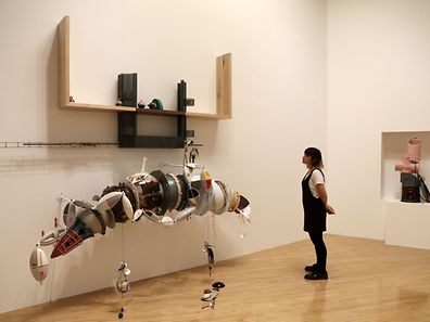 A woman looks at pieces of artwork forming an installation by artist Helen Marten