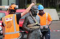 Workers remove a controversial statue of Captain John Fane Charles Hamilton from Civic Square in Hamilton on June 12, 2020, following a formal request by the Waikato-Tainui iwi (tribal confederation) and threats it would be torn down during a Black Lives Matter march due to take place the following day. - The statue of Hamilton, a British military commander who led a detachment against Maori during the Battle of Gate Pa in 1864, was removed as statues of colonial figures in Britain, Belgium and the United States were toppled by demonstrators amid worldwide protests against police brutality and racism in the wake of African American George Floyd's killing by a white police officer. (Photo by MICHAEL BRADLEY / AFP)