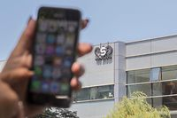 """(FILES) In this file photo taken on August 28, 2016, a woman uses her iPhone in front of the building housing the Israeli NSO group """"Pegasus"""", in Herzliya, near Tel Aviv. - An Israeli firm accused of supplying spyware to governments has been linked to a list of 50,000 smartphone numbers, including those of activists, journalists, business executives and politicians around the world, according to reports Sunday. (Photo by JACK GUEZ / AFP)"""