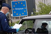 (FILES) In this file photo taken on April 19, 2020 a Belgian Police officer controls the documents of a person in a car at the border between Belgium and France during a police patrol in Quevy, enforcing the social distancing rules, as Belgium is in its fifth week of lockdown to fight the COVID-19 outbreak, caused by the novel coronavirus. - An European coordination for a return to free movement between European countries is delicate, between health imperatives and economic emergency, after the closings of the borders which have damaged a symbol of the European Union. (Photo by BENOIT DOPPAGNE / BELGA / AFP) / Belgium OUT