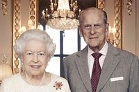 """In this photograph released by Buckingham Palace on November 18, 2017 and taken by Camera Press photographer Matt Holyoak in November 2017, Britain's Queen Elizabeth II and her husband, Britain's Prince Philip, Duke of Edinburgh pose between Thomas Gainsborough's 1781 portraits of George III and Queen Charlotte in the White Drawing Room at Windsor Castle, to mark their Platinum Wedding Anniversary (70 years). Queen Elizabeth II and Prince Philip will celebrate their platinum wedding anniversary on November 20, marking 70 years since they married in the splendour of Westminster Abbey. / AFP PHOTO / BUCKINGHAM PALACE/CAMERAPRESS / Matt Holyoak / RESTRICTED TO EDITORIAL USE - MANDATORY CREDIT """"AFP PHOTO / MATT HOLYOAK/CAMERAPRESS"""" - NO MARKETING NO ADVERTISING CAMPAIGNS - DISTRIBUTED AS A SERVICE TO CLIENTS - NOT FOR USE AFTER 2200 GMT ON DEC 2, 2017 - THE IMAGES MUST NOT BE ADAPTED, MANIPULATED, CROPPED, RE-TOUCHED OR RE-COLOURED"""