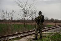 "A Greek army officer patrols at the railway station of Kastanies village, near the Greek-Turkish border on March 8, 2020. - Turkish President Recep Tayyip Erdogan said on March 8, 2020 he will hold talks in Brussels on March 9 as he called on Greece to ""open the gates"" to migrants. Thousands of migrants massed on the land border with Greece after Turkey last month said it would no longer prevent people from leaving the country. (Photo by ANGELOS TZORTZINIS / AFP)"