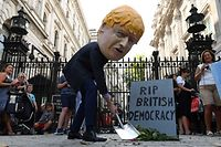 "A demonstrator, wearing a mask depicting Britain's Prime Minister Boris Johnson, and a mock gravestone inscribed with the words ""RIP British Democracy"" protests outside the gates to Downing Street in central London on August 28, 2019. - British Prime Minister Boris Johnson announced Wednesday that the suspension of parliament would be extended until October 14 -- just two weeks before the UK is set to leave the EU -- enraging anti-Brexit MPs. MPs will return to London later than in recent years, giving pro-EU lawmakers less time than expected to thwart Johnson's Brexit plans before Britain is due to leave the European Union on October 31. (Photo by DANIEL LEAL-OLIVAS / AFP)"