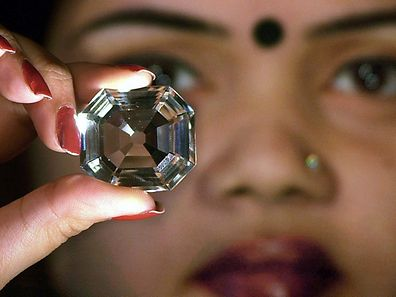 (FILES) - A file picture taken on January 29, 2002 shows an Indian model holding a replica of the famous Indian Koh-i-Noor diamond during a press conference in Kolkata. A Pakistani court is set on February 11, 2016 to hear a petition asking Britain's Queen Elizabeth II to return the Koh-i-Noor diamond more than 150 years after it was taken from Lahore by colonial forces.  AFP PHOTO / Deshakalyan Chowdhury / FILES
