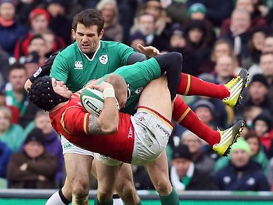 Wales' wing Tom James (C) is tackled by Ireland's wing Keith Earls during the Six Nations international rugby union match between Ireland and Wales at the Aviva Stadium in Dublin, Ireland, on Sunday.