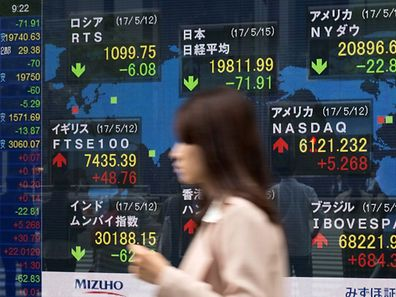 A woman walks past a quotation board displaying numbers of the world stock markets in front of a securities company in Tokyo on May 15, 2017.  Tokyo stocks opened lower on May 15 with a stronger yen pressuring exporter shares as geopolitical risks linger with North Korea's continued missile tests.   / AFP PHOTO / Kazuhiro NOGI