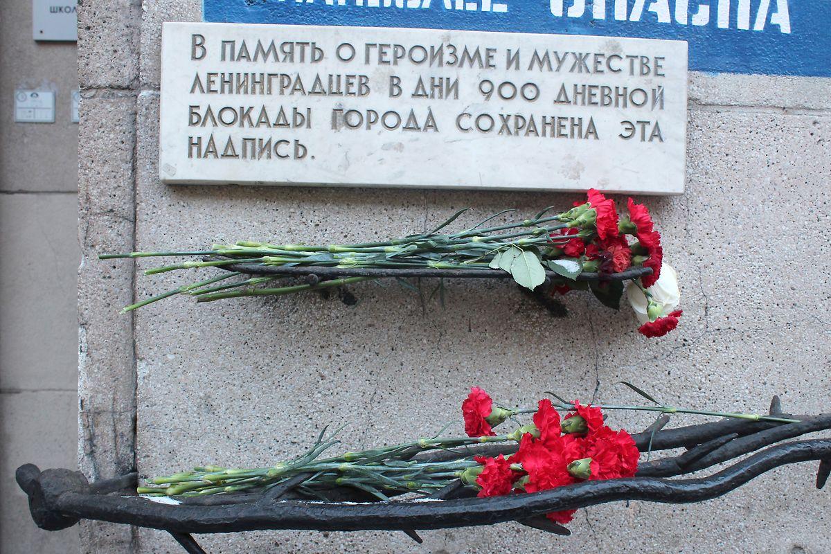 Rote Nelken liegen vor einem Gedenkstein an die Opfer der Blockade von Leningrad. Mehr als eine Million Zivilisten verhungerten und erfroren.