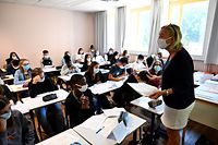 A teacher with protective mask speaks to pupils in a classroom in Brequigny high school in Rennes, western France, on September 1, 2020 on the first day of the school year amid the Covid-19 epidemic. - French pupils go back to school on September 1 as schools across Europe open their doors to greet returning pupils this month, nearly six months after the coronavirus outbreak forced them to close and despite rising infection rates across the continent. (Photo by Damien Meyer / AFP)