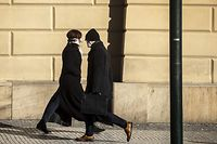 TOPSHOT - A man wearing a face mask walks past a woman with a face mask on March 23, 2020, in Prague, where most activities slowed down or came to a halt due to the spread of the novel coronavirus COVI-19. (Photo by Michal Cizek / AFP)