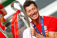 (FILES) This file photo taken on August 24, 2020 shows Bayern Munich's Polish forward Robert Lewandowski raising the European Champion Clubs' Cup during the trophy ceremony after winning at the end of the UEFA Champions League final football match between Paris Saint-Germain and Bayern Munich at the Luz stadium in Lisbon. - Bayern Munich striker Robert Lewandowski was named men's player of the year on December 17, 2020 at the FIFA's 'The Best' awards ceremony in Zurich. The 32-year-old Polish forward, top scorer in Europe and winner of the Champions League with Bayern, came out ahead of the other two nominees, Lionel Messi and Cristiano Ronaldo. (Photo by MATTHEW CHILDS / POOL / AFP)