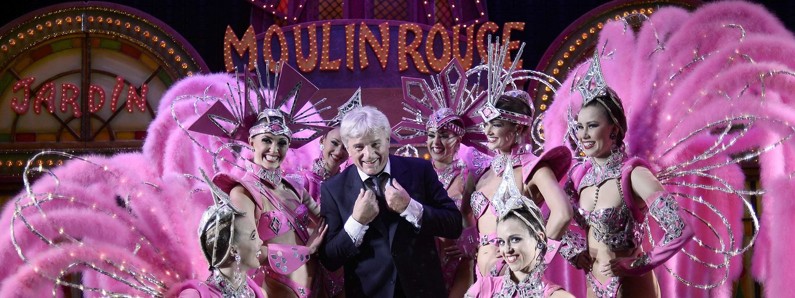 (FILES) This file photo taken on October 1, 2014 shows Jean-Jacques Clerico, owner and great great son of the founder of the Moulin Rouge posing with dancers at the Moulin Rouge cabaret in Paris. - French oldest cabaret, the Moulin Rouge, will celebrate its 130th anniversary on October 6, 2019. (Photo by STEPHANE DE SAKUTIN / AFP)