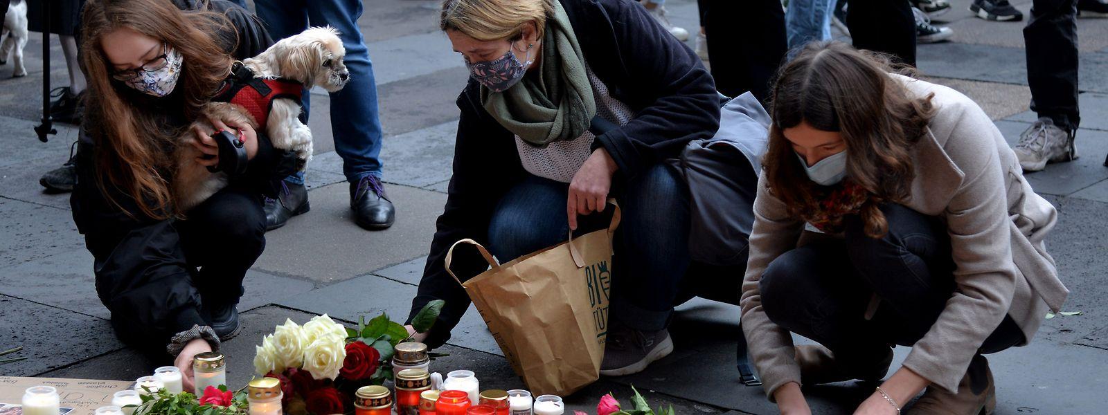 Trauernde legen nach der Amokfahrt mit fünf Toten inTrier an der Porta Nigra Kerzen und Blumen nieder.