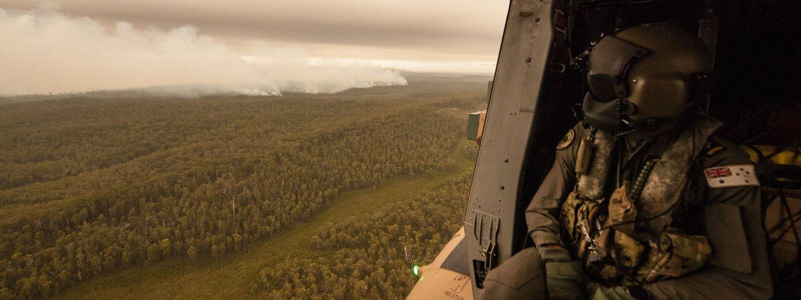 Ein Besatzungsmitglied blickt aus einem Hubschrauber der australischen Navy auf einen Buschbrand in der Region Gippsland im Bundesstaat Victoria.