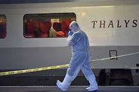 Police walks on a platform next to a Thalys train of French national railway operator SNCF at the main train station in Arras, northern France, on August 21, 2015. A gunman opened fire on a train travelling from Amsterdam to Paris, injuring three people before being overpowered by passengers, French state rail company SNCF and rescue services said. Two of the victims were seriously injured and at least one suffered gunshot wounds, an SNCF spokesman said, adding that the assailant was armed with guns and knives. The motives behind the attack were not immediately known. AFP PHOTO / PHILIPPE HUGUEN