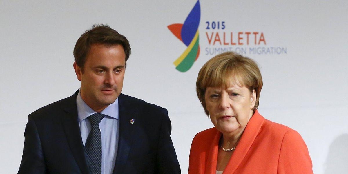 O primeiro-ministro do Luxemburgo com Angela Merkel, à chegada à cimeira euro-africana sobre migrações, em Malta