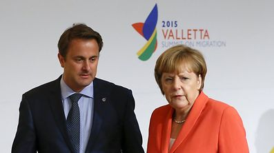 Luxembourg Prime Minister Xavier Bettel (L) and German Chancellor Angela Merkel attend the Valletta Summit on Migration in Valletta, Malta, November 11, 2015. Leaders of the European Union met African counterparts on Malta on Wednesday, hoping pledges of cash and other aid can slow the flow of migrants crossing the Mediterranean from the world's poorest continent to wealthy Europe.   REUTERS/Yves Herman