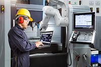Maintenance engineer using laptop computer control automatic robotic hand with CNC machine in smart factory, Industry 4.0 concept - Image