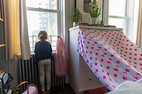 On 2 April 2020, Margot, 4, looks out the window down to the street from her family's apartment in New York City, United States of America. On a weekday she would normally be at daycare with her friends, but Margot, along with more than 1 million New York City children and youth, has been staying healthy at home with her family for weeks, with the city largely shut down as a preventative measure against the further spread of coronavirus (COVID-19).