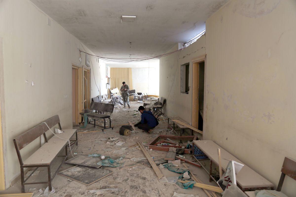 Zwei Personen durchsuchen die Trümmer in einem Krankenhaus nach den Luftangriffen der syrischen Regierung.