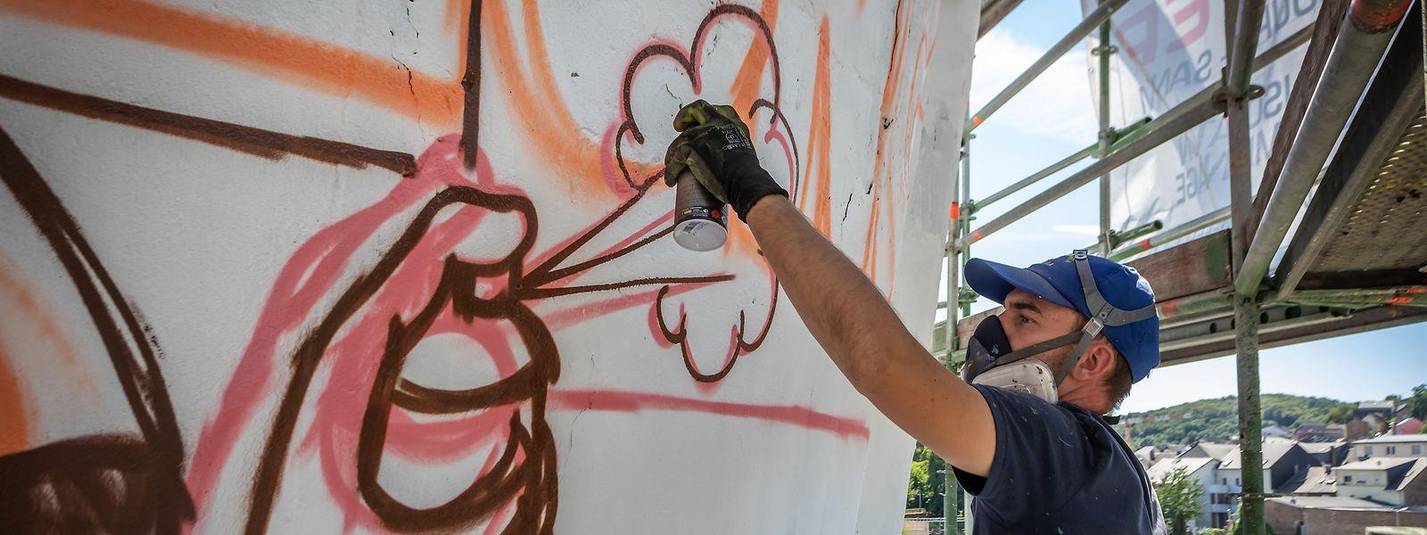 """Chaque jour, Alain Welter passe jusqu'à dix heures à tagger la monumentale """"toile"""" de ciment qui lui a été confiée."""