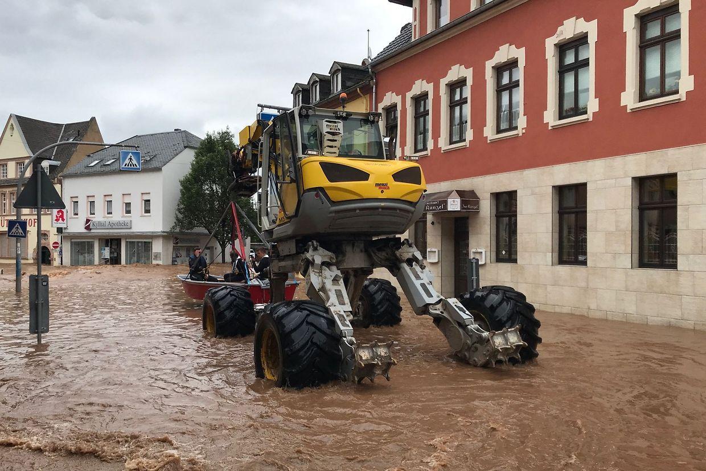 Um barco de salvamento (C L) é transportado por um veículo especial no bairro inundado de Ehrang em Trier, no oeste da Alemanha.