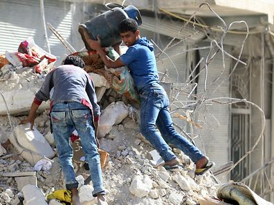 People remove belongings from a damaged site after an air strike in the rebel-held besieged al-Qaterji neighbourhood of Aleppo, Syria October 17, 2016.