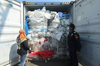Indonesian officers check a container full with illegal imported plastics waste in Batam on July 29, 2019. - Indonesia has returned seven shipping containers of illegally imported waste to France and Hong Kong, an official. (Photo by SEI RATIFA / AFP)