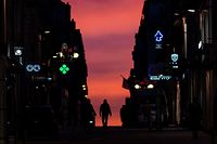 A man walks down an empty street in Nantes as the sun sets during the nationwide 18:00 overnight curfew restrictions taken to curb the spread of the Covid-19 pandemic, on February 4, 2021. (Photo by LOIC VENANCE / AFP)