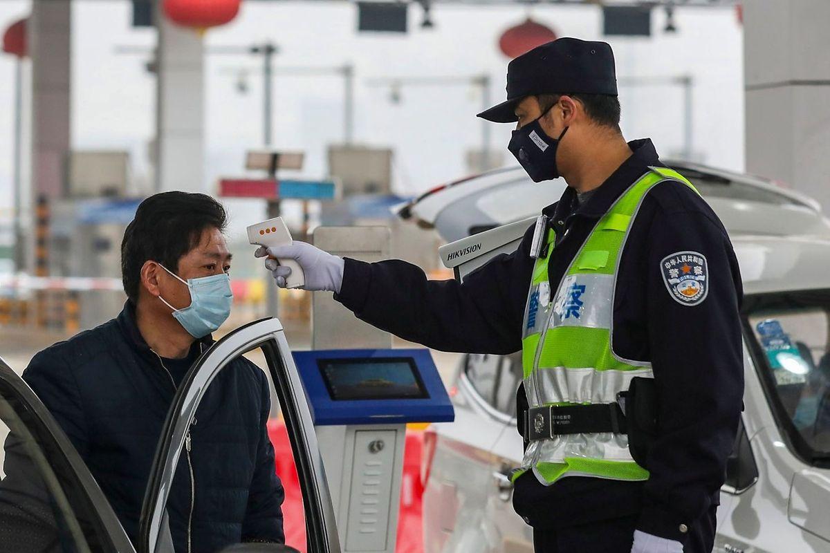 Ein Polizist überprüft die Körpertemperatur eines Autofahrers auf einer Autobahn in Wuhan. In China stehen wegen des Kampfes gegen die Virus-Ausbreitung 13 Städte unter Quarantäne.