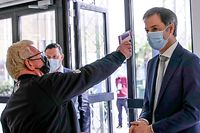 Belgian Prime Minister Alexander De Croo gets his temperature checked during a visit to the vaccination village setup in the Heysel site of the Brussels Expo exhibition halls in Brussels on April 15, 2021. (Photo by OLIVIER HOSLET / BELGA / AFP) / Belgium OUT