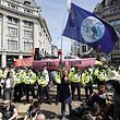 A climate change activist waves a flag as police officers keep watch during the ocupation of the road junction at Oxford Circus in central London on April 19, 2019, the fifth day of an environmental protest by the Extinction Rebellion group. - Undeterred by over 400 arrests, climate change activists continued their demonstration into a fifth day in London with a small protest at the country's main Heathrow Airport, along with the ongoing protest camps at other iconic locations around the British capital. (Photo by Tolga AKMEN / AFP)