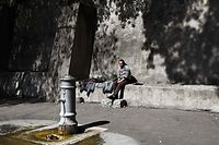 A homeless man sits on a ledge by a public fountain at Piazza della Consolazione in central Rome on March 19, 2020 during the country's lockdown following the new coronavirus pandemic. (Photo by Vincenzo PINTO / AFP)