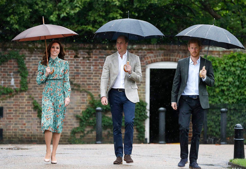 Herzogin Kate, Prinz William und Prinz Harry auf dem Weg zum Garten des Kensington-Palasts, der zum Gedenken in diesem Jahr ganz in Weiß erblüht.