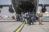 """TOPSHOT - In this handout image courtesy of the US Marine Corps, Families begin to board a US Air Force Boeing C-17 Globemaster III during an evacuation at Hamid Karzai International Airport, Kabul, Afghanistan, August 23, 2021. (Photo by Samuel RUIZ / US MARINE CORPS / AFP) / RESTRICTED TO EDITORIAL USE - MANDATORY CREDIT """"AFP PHOTO / SAMUEL RUIZ / US MARINE CORPS """" - NO MARKETING - NO ADVERTISING CAMPAIGNS - DISTRIBUTED AS A SERVICE TO CLIENTS"""