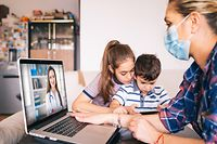 Mother trying to talk with doctor on laptop while watching two kids.Family in isolation covid-19