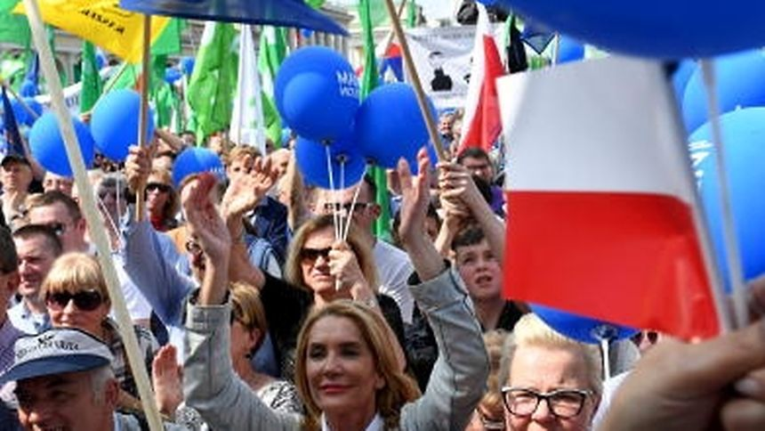 Demonstrators hold Polish and EU flags during the ìFreedom Marchî in the Polish capital Warsaw on May 6, 2017 organised by Poland's main liberal Civic Platform (PO) opposition party to protest against the rightwing nationalist Law and Justice (PiS) government over alleged rule of law violations. / AFP PHOTO / Janek SKARZYNSKI