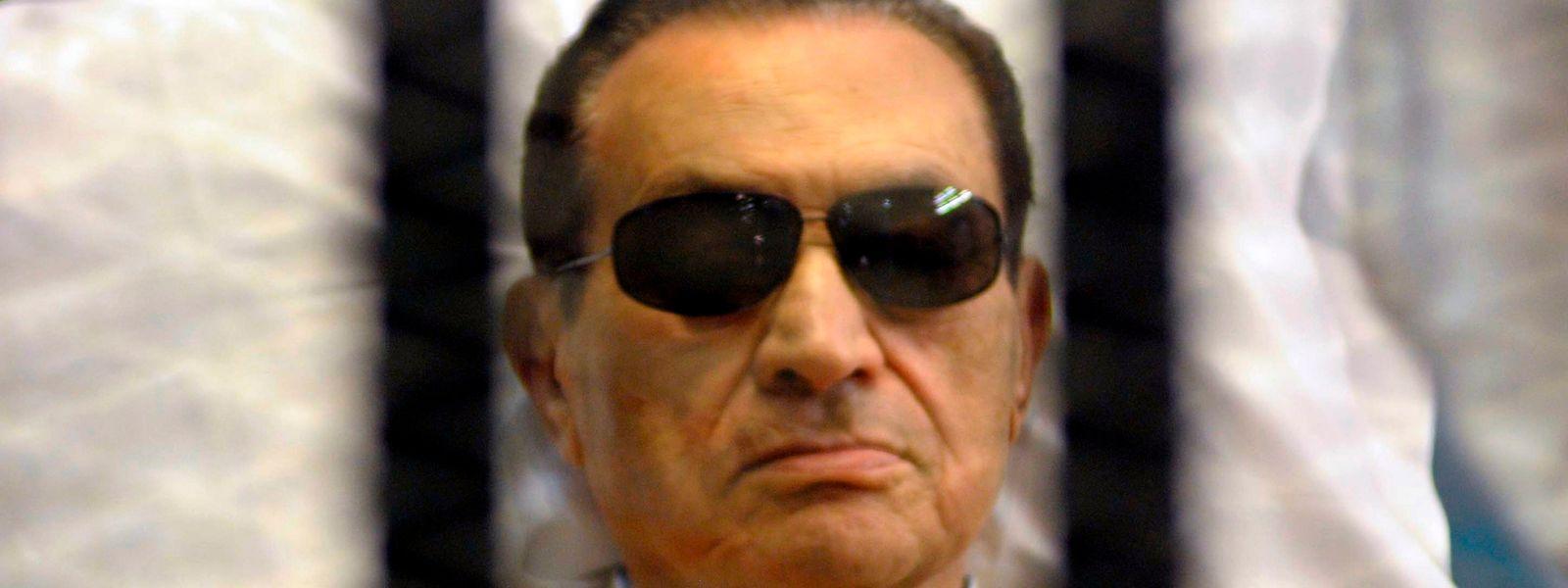 Auf eine Trage gestützt, folgt der frühere ägyptische Präsident Husni Mubarak im Juni 2012 seinem Prozess im Gerichtssaal in der Polizeiakademie von Kairo.