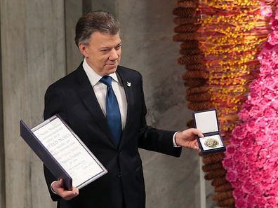 Nobel Peace Prize laureate Colombian President Juan Manuel Santos poses with the medal and diploma during the Peace Prize awarding ceremony at the City Hall in Oslo on December 10, 2016.
