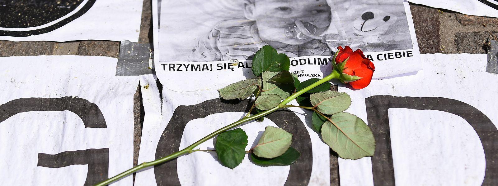 Anteilnahme: Eine rote Rose liegt im polnischen Krakau auf Zetteln mit den Buchstaben GOD und einem Foto des kranken britischen Jungen Alfie.