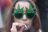 "(FILES) In this file photo taken on April 20, 2017 A woman smokes marijuana on Parliament Hill on 4/20 in Ottawa, Ontario, April 20, 2017. About 4.9 million Canadians spent a whopping Can$5.7 billion (US$4.6 billion) on cannabis last year, the government's statistical agency said on January 25, 2018.Its production in terms of value is now ""on par with the beer industry and larger than the tobacco industry,"" according to Statistics Canada's estimates.  / AFP PHOTO / Lars Hagberg"