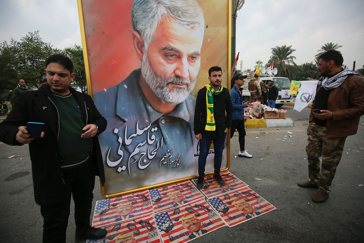 "Supporters of the Hashed al-Shaabi paramilitary force and Iraq's Hezbollah brigades pose for a picture next to a poster of Iranian military commander Qasem Soleimani (portrait) during a funeral, for Soleimani and Iraqi paramilitary chief Abu Mahdi al-Muhandis killed in a US air strike, in Baghdad's district of al-Jadriya, in Baghdad's high-security Green Zone, on January 4, 2020. - Thousands of Iraqis chanting ""Death to America"" joined the funeral procession for Iranian commander Qassem Soleimani and Iraqi paramilitary chief Abu Mahdi al-Muhandis, both killed in a US air strike. The cortege set off around Kadhimiya, a Shiite pilgrimage district of Baghdad, before heading to the Green Zone government and diplomatic district where a state funeral was to be held attended by top dignitaries. In all, 10 people -- five Iraqis and five Iranians -- were killed in Friday morning's US strike on their motorcade just outside Baghdad airport. (Photo by Ahmad AL-RUBAYE / AFP)"
