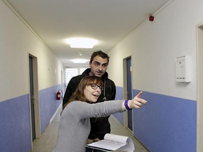 Illustration photo of a woman giving a resident directions at a temporary shelter for asylum seekers