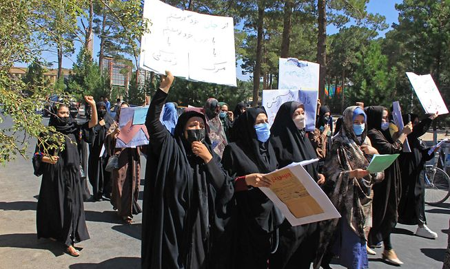 Afghan women hold placards as they take part in a protest in Herat on September 2, 2021