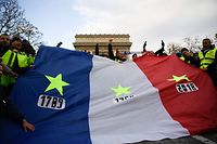 """Protestors wearing """"yellow vests"""" (gilets jaunes) hold a French flag with yellow stars near the Arc de Triomphe in Paris on December 8, 2018 during a protest against rising costs of living they blame on high taxes. - Paris was on high alert on December 8 with major security measures in place ahead of fresh """"yellow vest"""" protests which authorities fear could turn violent for a second weekend in a row. (Photo by Bertrand GUAY / AFP)"""