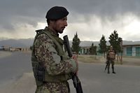 Afghan National Army (ANA) soldiers stand guard at a checkpoint near the a US military base in Bagram, some 50 km north of Kabul on April 29, 2021. (Photo by WAKIL KOHSAR / AFP)