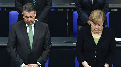 German Chancellor Angela Merkel (R) and German Vice Chancellor and Foreign Minister Sigmar Gabriel stand in tribute to late former German Chancellor Helmut Kohl on June 22, 2017 at the Bundestag (lower house of parliament) in Berlin. Helmut Kohl, the former German chancellor who seized the chance to reunite his country after years of Cold War separation, died at the age of 87 on June 16, 2017. / AFP PHOTO / John MACDOUGALL / ALTERNATIVE CROP