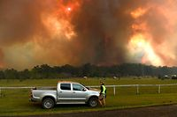 Locals watch as bushfires impact on farmland near the small town of Nana Glen, some 600kms north of Sydney on November 12, 2019. - Bushfires reached within kilometres (miles) of Sydney's city centre prompting firefighting planes to spray red retardant over trees and houses in a northern suburb. (Photo by WILLIAM WEST / AFP)