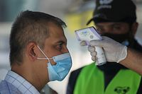 A costumer, wearing a protective mask due to the COVID-19 pandemic, has his temperature checked before entering a supermarket in the Iraqi capital Baghdad, on June 23, 2020. (Photo by AHMAD AL-RUBAYE / AFP)