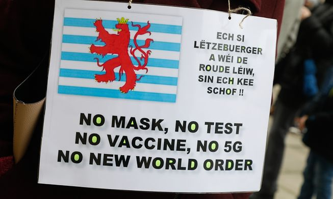 A demonstrator in Luxembourg connects Covid mask and test mandates to global conspiracy plots
